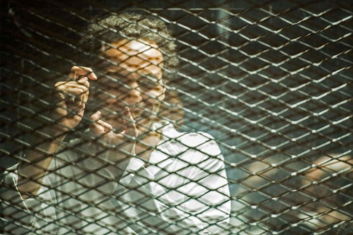 Egyptian photojournalist Mahmoud Abu Zeid, widely known as Shawkan, mimes a photographer inside a soundproof glass dock during his trial in the capital Cairo, on September 8, 2018. AFP