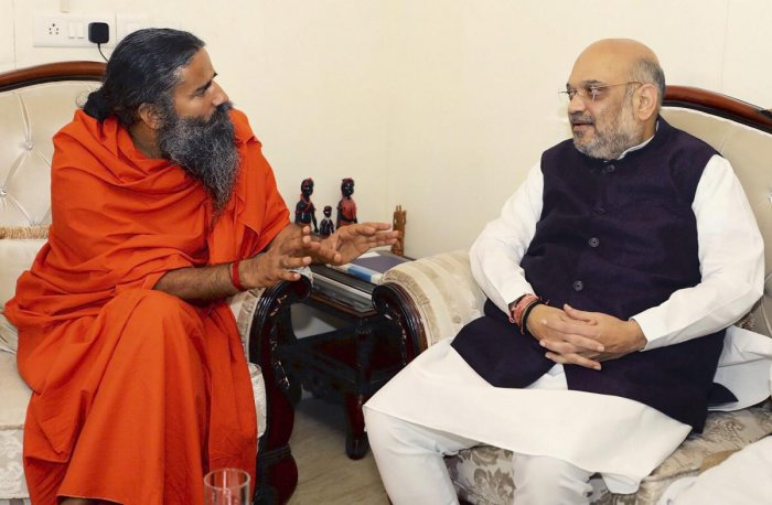 BJP President Amit Shah meets yoga guru Baba Ramdev during his 'Sampark for Samarthan' campaign in New Delhi on Monday. PTI