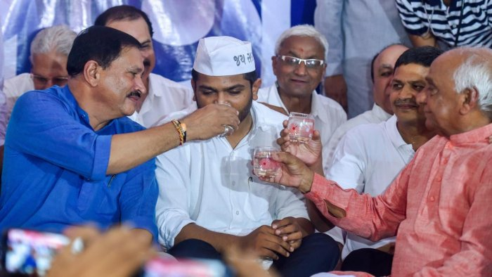 Patidar leaders C K Patel Patidar, Naresh Patel and Pralhad Patel offer coconut water to Patidar Anamat Andolan Samiti (PAAS) leader Hardik Patel to break his 19-day long indefinite hunger strike, in Ahmedabad, on Wednesday. PTI