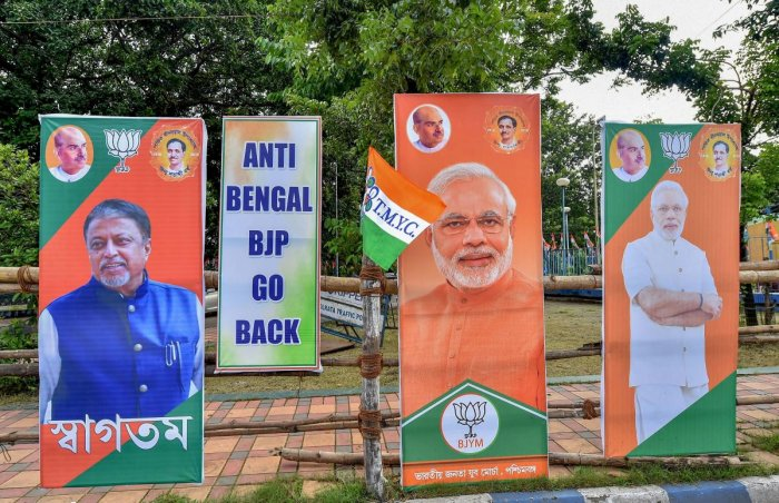 """TMC activists hang a poster with the slogan """"Anti-Bengal BJP Go Back"""" along with the posters of BJP leaders. PTI file photo"""