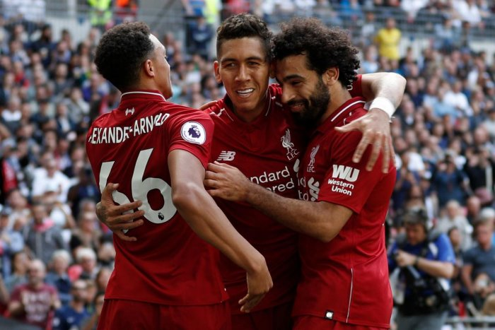 Fantastic run: Liverpool's Roberto Firmino (centre) celebrates with Trent Alexander-Arnold (left) and Mohamed Salah after scoring against Tottenham Hotspur on Saturday. AFP