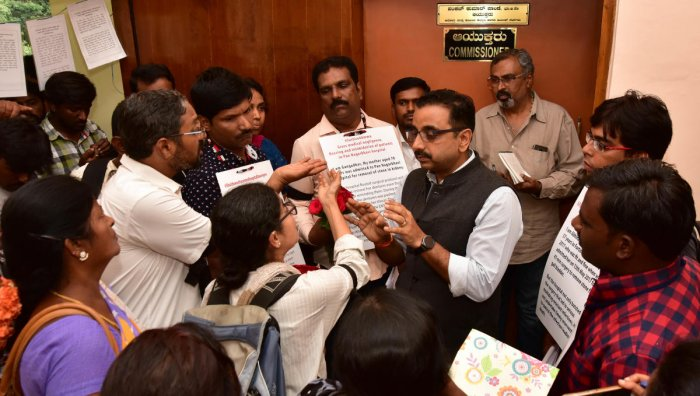 Relatives of patients misdiagnosed by doctors present roses to Pankaj Kumar Pandey, Commissioner, Health and Family Welfare, for the delay in enforcing the KPME Act in Bengaluru on Saturday. (DH PHOTO/RANJU P)