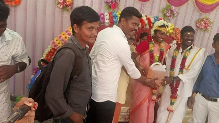 Ilanchezhian and Kanimozhi, newly wed couple, accepting 'costliest gift' of 5 litres of petrol from their friends on Sunday. DH Photo