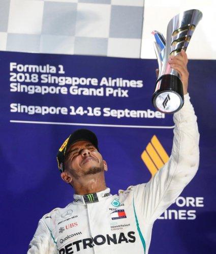 TOO GOOD: Mercedes' Lewis Hamilton celebrates on the podium after winning the Singapore GP on Sunday. REUTERS