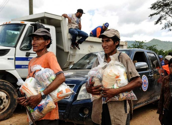 Honduran Tolupan natives and ladino people, receive food donations from the government at the Montana de la Flor, in Francisco Morazan department, Honduras on September 01, 2018. - At least 600 families from five different indigenous communities are facing starvation due to the loss of their crops, after the sever droughts caused by the El Nino climate phenomenon. AFP