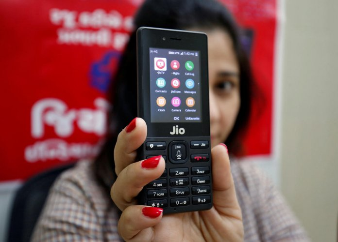 A sales person displays JioPhone as she poses for a photograph at a store of Reliance Industries' Jio telecoms unit. REUTERS