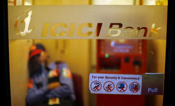 FILE PHOTO: A private security guard sleeps inside an automated teller machine (ATM) booth of ICICI bank in New Delhi. Reuters