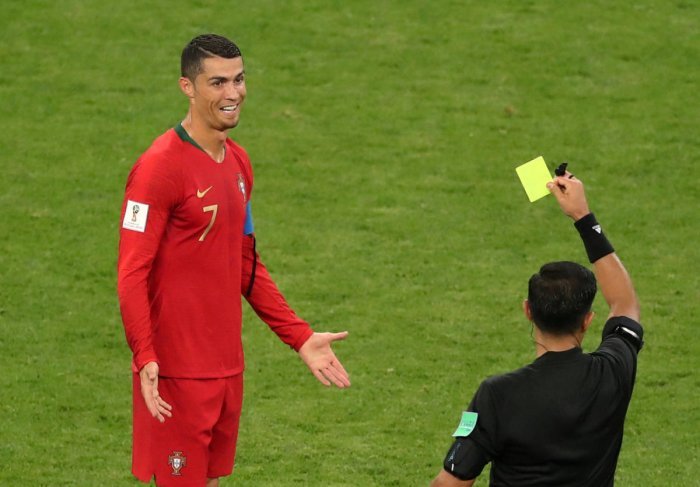 Cristiano Ronaldo is shown a yellow card by referee Enrique Caceres for an elbowing incident after a VAR review. REUTERS