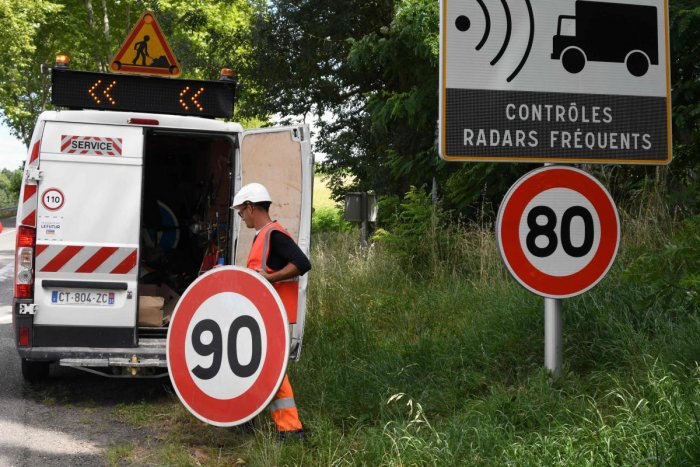 An employee of the Interdepartmental Directions of Roads sets an 80 kmph speed limit sign up on the national road RN2 in Grenade, south-western France. (AFP)