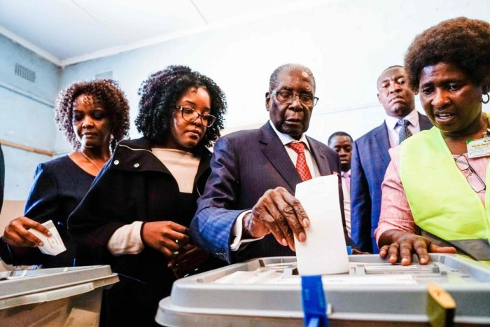 Former Zimbabwean president Robert Mugabe (centre) his daughter Bona and wife Grace cast their votes at a polling station at a primary school in the Highfield district of Harare during the country's general elections on July 30, 2018. AFP