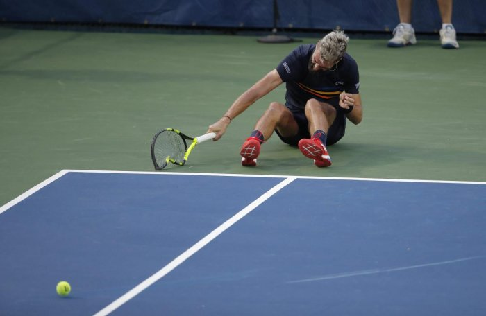 Benoit Paire smashes his racquet during his match against Marcos Baghdatis