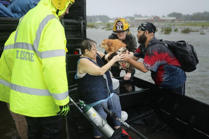 Rescue workers and volunteers help rescue a woman and her dog from their flooded home during Hurricane Florence in James City, United States, on September 14, 2018. AFP