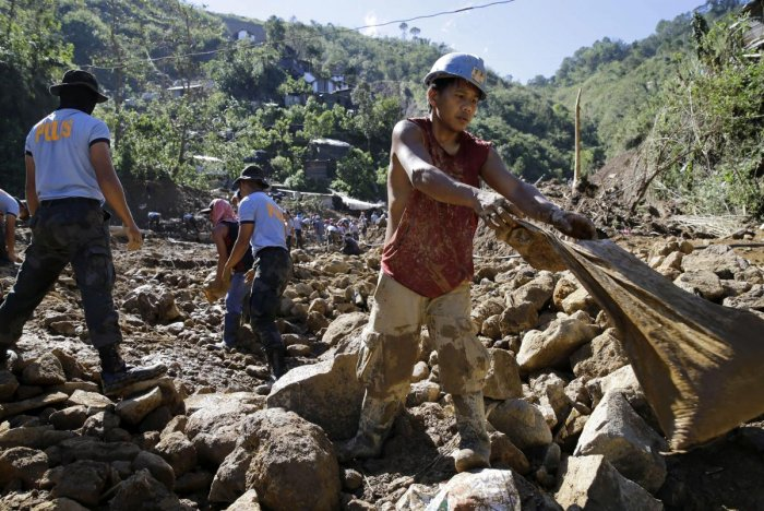A Filipino miner, right, joins search operations at the site where victims are believed to have been buried by a landslide triggered by Typhoon Mangkhut as it lashed across Itogon, Benguet province, northern Philippines, Tuesday, Sept. 18, 2018. (AP/PTI P