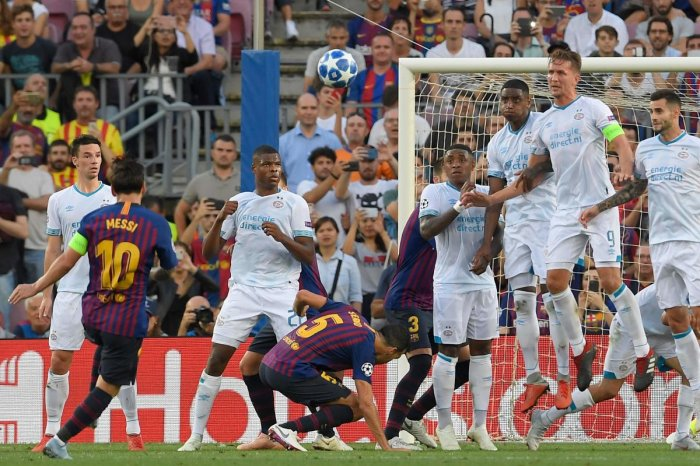 STUNNER: Barcelona's Lionel Messi (left) scores off a freekick during their clash against PSV Eindhoven at Camp Nou on Tuesday. AFP