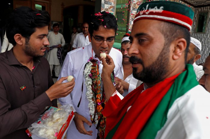 Supporters of Imran Khan, chairman of the Pakistan Tehreek-e-Insaf (PTI) party, offer sweets to each other as they celebrate a day after the general election, in Peshawar, Pakistan on Thursday. (REUTERS/Fayaz Aziz)