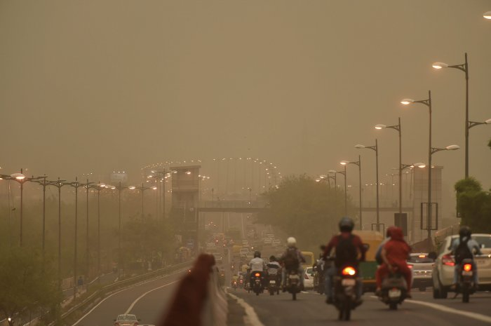 Vehicles ply slowly on a road as the weather turns hazy, in New Delhi on Tuesday. PTI