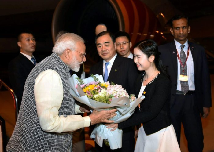 Prime Minister Narendra Modi being welcomed on his arrival in Wuhan, China on Thursday. Chinese Vice Foreign Minister Kong Xuanyou is also seen. PTI Photo