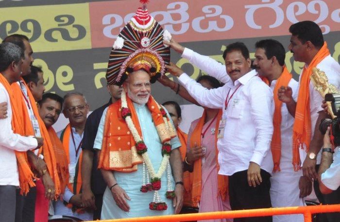 Prime Minister Narendra Modi being felicitated with a Badaguthittu yakshagana headgear in Udupi on Tuesday.