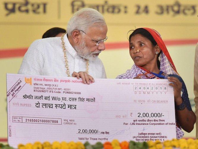 Prime Minister Narendra Modi hands over the cheque of Rs. 2 Lac to Nanhi Bai Marko, under Pradhan Mantri Jeevan Jyoti Beema Yojana during the National Panchayati Raj Day 2018, at Mandla in Madhya Pradesh. PTI Photo
