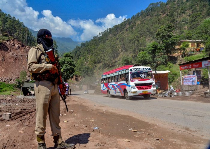 Security personnel stand guard as a bus full of pilgrims moves towards the holy cave shrine of Amarnath in the Pahalgam district of Jammu and Kashmir on July 2, 2018. (PTI File Photo)