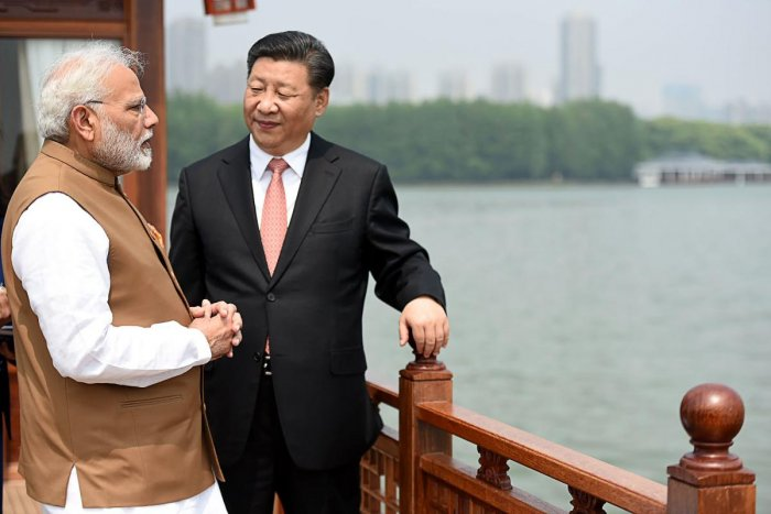 This handout photograph released by India's Press Information Bureau (PIB) on April 28, 2018 shows India's Prime Minister Narendra Modi (L) and Chinese President Xi Jinping looking on in a house boat, at East Lake, in Wuhan. Chinese President Xi Jinping a