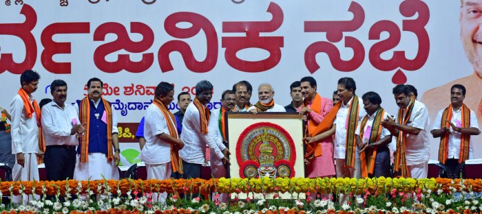 BJP leaders felicitate Narendra Modi with a Thenkuthittu Yakshagana headgear, made by Mahalasa Art School student Soumya, during the public rally at Nehru Maidan in Mangaluru on Saturday.