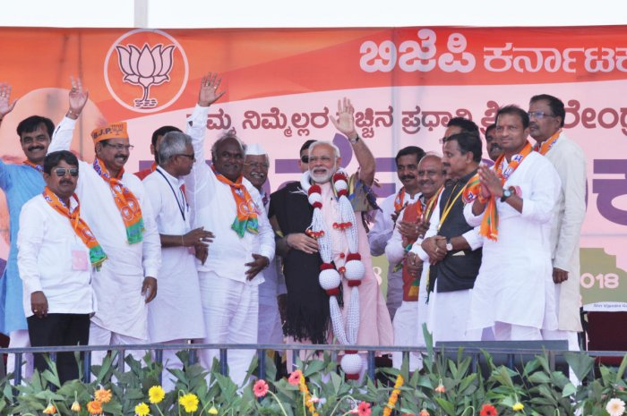 Prime Minister Narendra Modi is felicitated by presenting him a blanket during an election rally in Saravada village of Vijayapura taluk on Tuesday. DH Photo