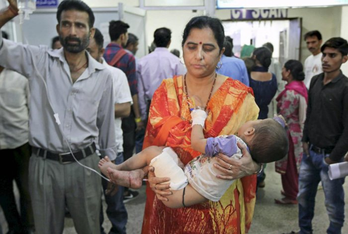 A woman carries her son, who was injured in cross-border firing, to a hospital in Jammu on Wednesday. PTI