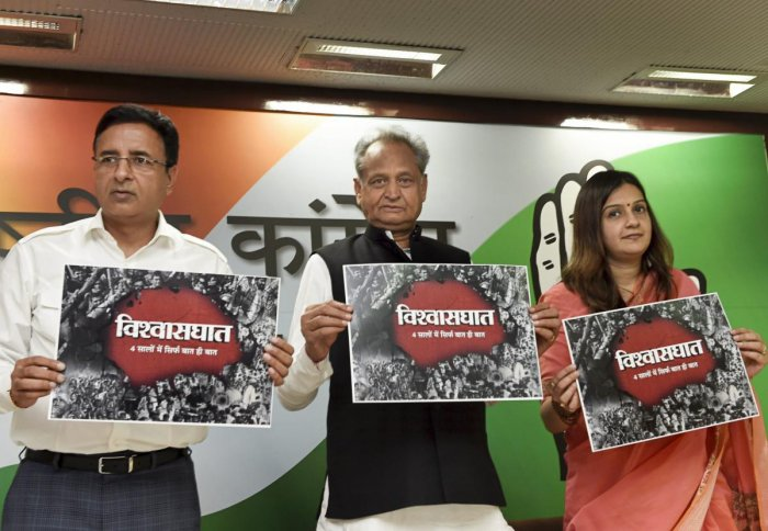 Senior Congress leader Ashok Gehlot with AICC spokespersons Randeep Singh Surjewala and Priyanka Chaturvedi release a poster before a press conference, in New Delhi, on Wednesday. PTI