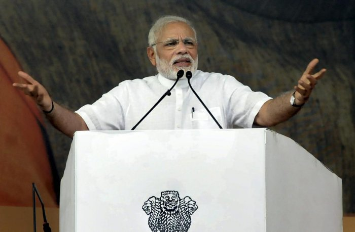 Prime Minister Narendra Modi addresses during the foundation stone laying ceremony of several projects, at Baliapur block of Dhanbad district, in Jharkhand, on Friday. (PTI Photo)