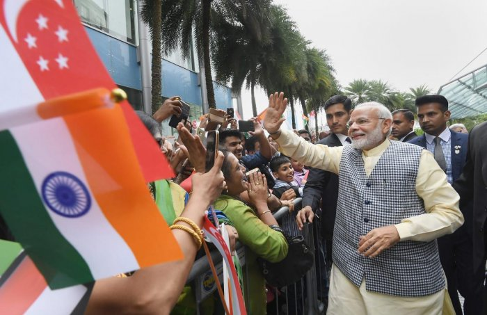 Prime Minister Narendra Modi being welcomed by the members of Indian community on his arrival, in Singapore. PTI Photo/PIB