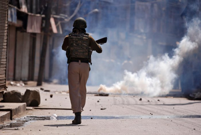 An policeman chases protesters amid tear gas smoke during a protest after Jumat-ul-Vida or the last Friday prayers of the holy fasting month of Ramadan, in Srinagar. (Reuters file photo)