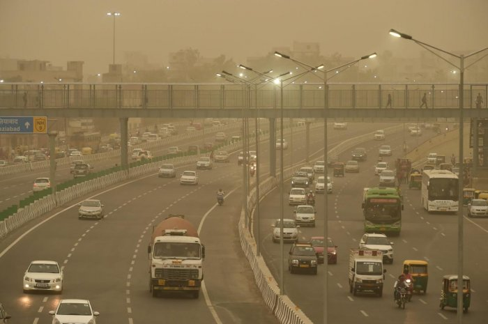 Vehicles ply slowly on a road as the weather turns hazy, in New Delhi. PTI