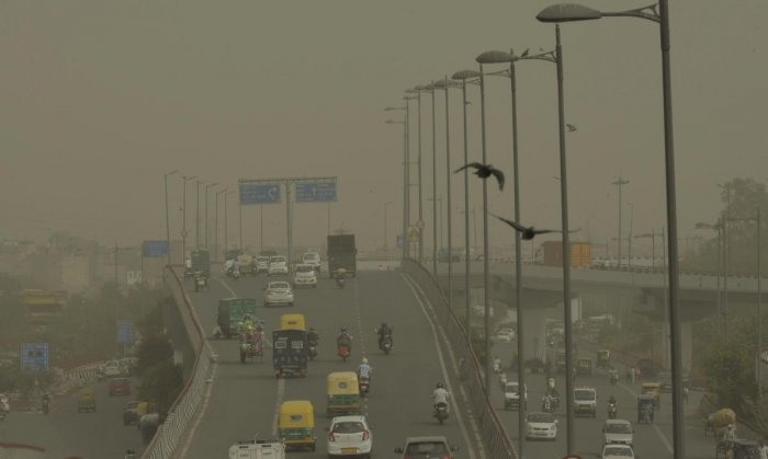 Vehicles ply slowly on a road as dust envelopes the sky over New Delhi, on Wednesday. PTI Photo