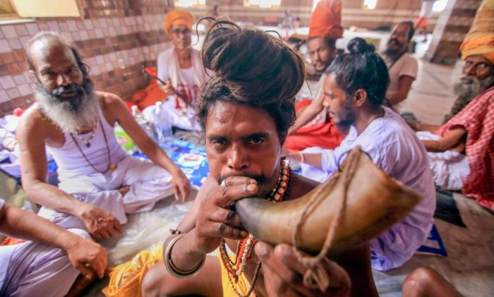 A Sadhu blows a buffalo-horn as they wait to register for the Amarnath Yatra, at Ram Mandir Basecamp in Jammu. PTI