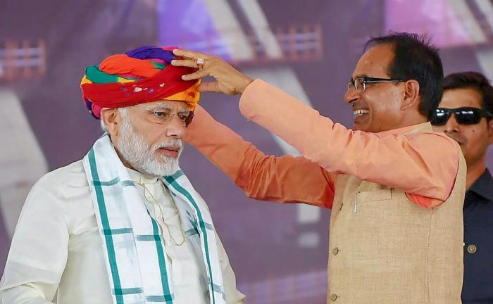 Prime Minister Narendra Modi being presented a turban by Madhya Pradesh Chief Minister Shivraj Singh Chouhan during the inauguration of Mohanpura Irrigation Project, in Rajgarh on Saturday. PTI