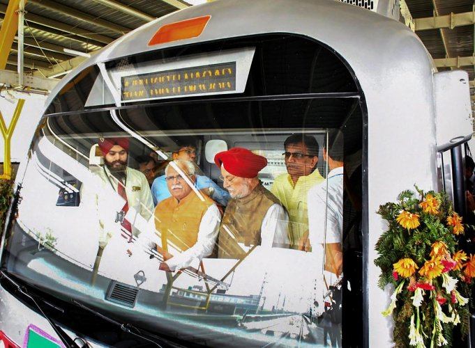 Haryana Chief Minister Manohar Lal Khattar and Union Urban Affairs Minister Hardeep Puri in the cockpit of a metro train after the inauguration of the 11.2-km-long fully-elevated Mundka-Bahadurgarh section of the Delhi Metro's Green Line by Prime Minister Narendra Modi. PTI photo.