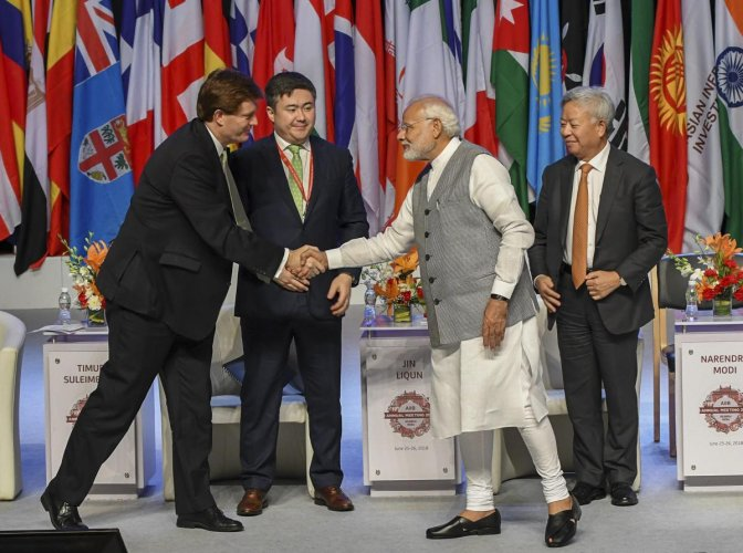 Prime Minister Narendra Modi greets the delegates after delivering his inaugural speech for the third annual meeting Asian Infrastructure Investment Bank (AIIB) Forum, as AIIB President Jin Liqun (R) looks on, in Mumbai on Tuesday, June 26, 2018.