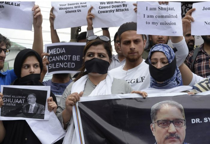 Journalists stage a protest against the killing of veteran journalist Shujaat Bukhari and recent remarks by BJP leader Lal Singh that were denounced as a threat towards media workers in Kashmir, in Srinagar on Tuesday. (AFP)