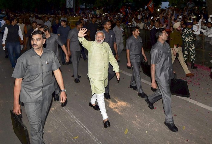 Prime Minister Narendra Modi, surrounded by security personnel, waves at the crowd during an event at the then BJP headquarters in New Delhi. (PTI file photo)