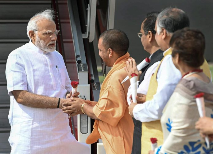 Prime Minister Narendra Modi being greeted by Uttar Pradesh Chief Minister Yogi Adityanath, on his arrival in Lucknow on Thursday. (PTI Photo)