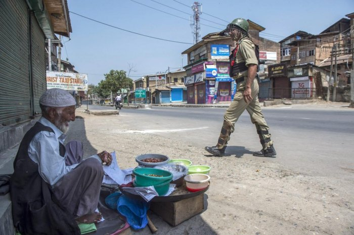 A security personal walks past a vendor during the second day of strike called by separatist leaders against the petitions filed in the Supreme court challenging the validity of Article 35A, in Srinagar. (PTI file photo)