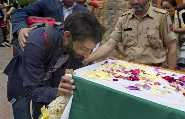 Brother of slain SG Constable Parvaiz Ahmad cries as he lays a wreath on the latter's coffin during a wreath-laying ceremony at District Police Lines, in Srinagar, on Sunday. PTI