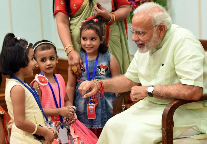 Children ties rakhi on Prime Minister Narendra Modi on the occasion of Raksha Bandhan festival, in New Delhi on Sunday, Aug 26, 2018. (PIB Photo via PTI)