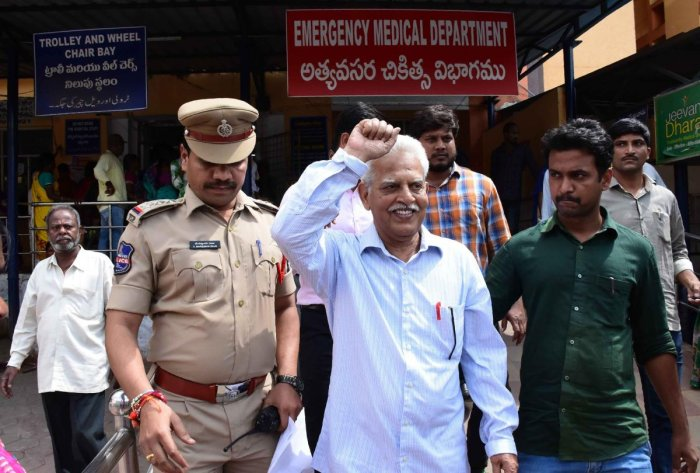 Poet and activist Varara Rao (C) gestures as he is escorted by policemen as he is arrested in Hyderabad. Police arrested prominent lawyers and left-wing activists Tuesday for alleged links to Maoist rebels, drawing a rebuke from rights watchdogs who label
