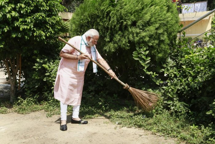 Prime Minister Narendra Modi undertakes a cleanliness drive under 'Swachhta Hi Sewa' campaign in the premises of Baba Sahib Ambedkar Higher Secondary School at Paharganj, New Delhi, on Saturday. PTI
