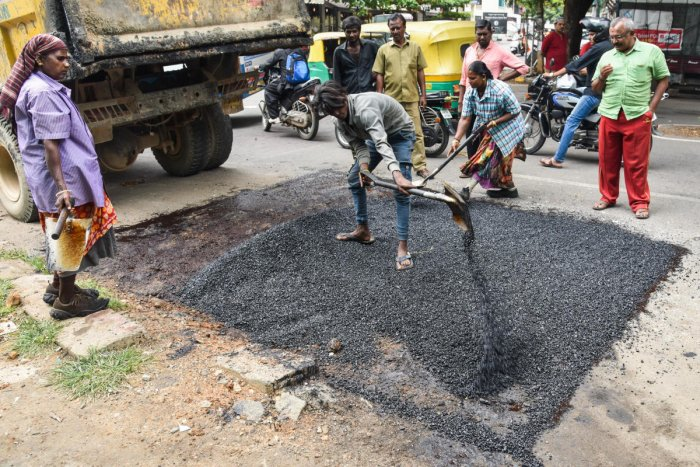 BBMP workers filling the potholes in Jayanagar 4T Block on Friday. DH photo/S K Dinesh