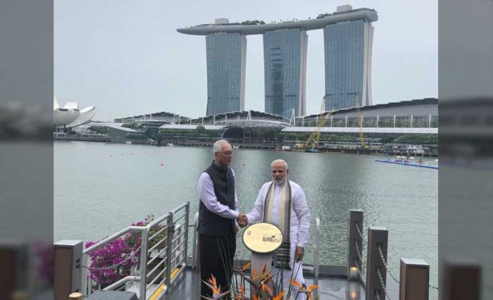 Prime Minister Narendra Modi and Singapore's former premier Goh Chok Tong jointly unveils a plaque to pay tribute at the immersion site of Mahatma Gandhi's ashes at Clifford Pier. (Twitter/PMO India)