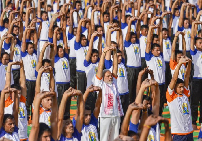 Prime Minister Narendra Modi performs yoga along with thousands of others during a mass yoga event on 4th International Yoga Day at Forest Research Institute (FRI) ground in Dehradun, on Thursday. (PTI Photo/Manvender Vashist)
