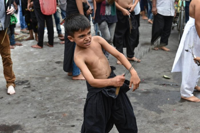 Lucknow: A Shia Muslim boy flagellates himself while participating in a Muharram procession in Lucknow, Friday, Sept 21, 2018. (PTI Photo/Nand Kumar)
